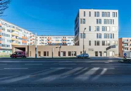 Durch den Business Point wird der Hof der Wohnhäuser aus den 60-er Jahren vom Schall der stark befahrenen Eberhard Fugger Straße geschützt.